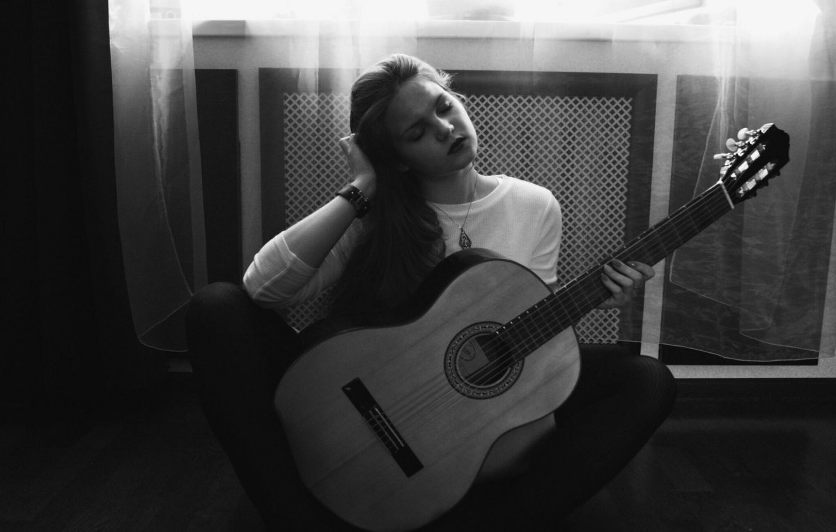 Foto in bianco e nero di una ragazza con la chitarra classica